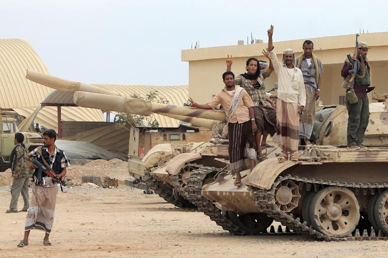Fighters from local tribes, Popular Resistance Committees and supporters of the southern Yemeni separatist movement, who oppose the Shiite-Huthi movement, stand on a tank at the Al-Anad airbase, north of Aden, on March 24, 2015