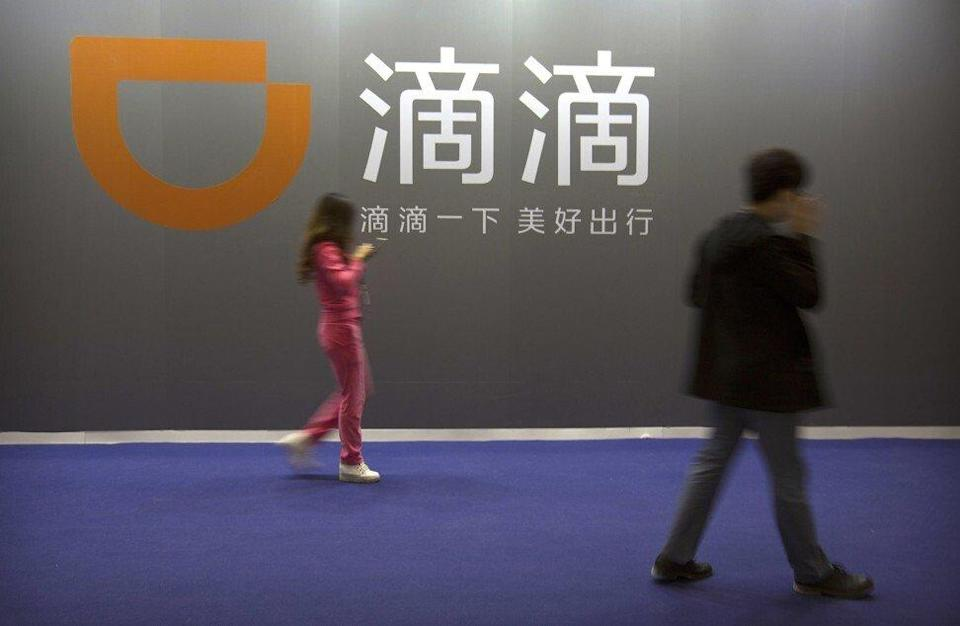 Visitors walk past a sign for Chinese ride-hailing service Didi Chuxing at the Global Mobile Internet Conference in Beijing. Photo: AP Photo