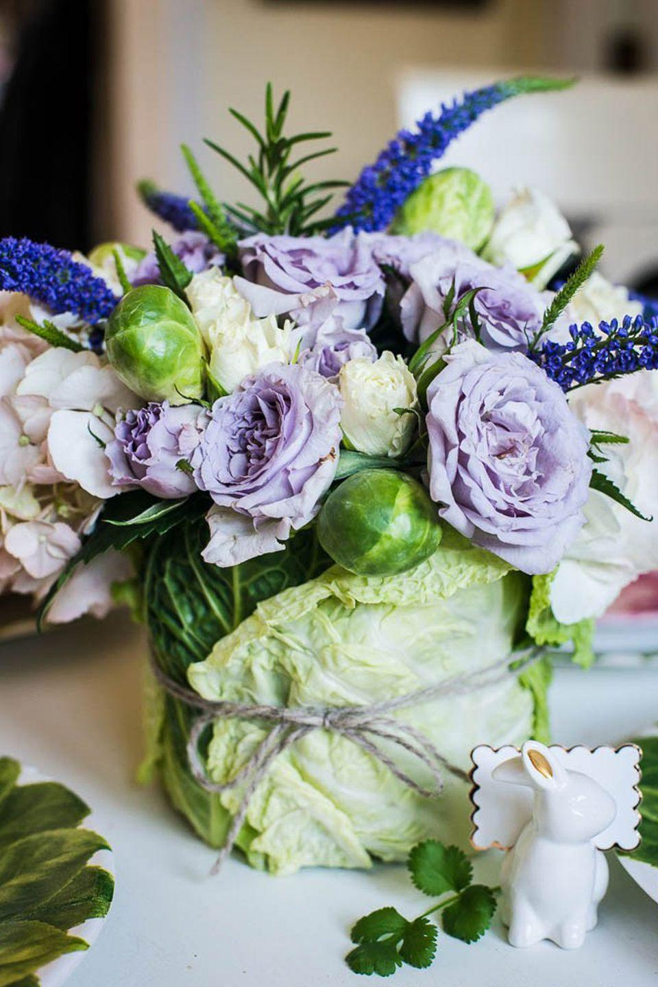 """<p>Both cabbage <em>and </em>brussels sprouts were used to turn a small assortment of purple and white flowers into this unforgettable centerpiece.</p><p><em><a href=""""http://celebratingeverydaylife.com/diy-easter-cabbage-arrangement-tutorial/"""" rel=""""nofollow noopener"""" target=""""_blank"""" data-ylk=""""slk:Get the tutorial at Celebrating Everyday Life »"""" class=""""link rapid-noclick-resp"""">Get the tutorial at Celebrating Everyday Life »</a></em></p><p><strong><em>Seletti Melania Hybrid Vase, $215</em></strong> <a class=""""link rapid-noclick-resp"""" href=""""https://go.redirectingat.com?id=74968X1596630&url=https%3A%2F%2Fwww.2modern.com%2Fproducts%2Fhybrid-melania-vase&sref=https%3A%2F%2Fwww.housebeautiful.com%2Fentertaining%2Fflower-arrangements%2Fg19409803%2Feaster-flower-arrangements%2F"""" rel=""""nofollow noopener"""" target=""""_blank"""" data-ylk=""""slk:BUY NOW"""">BUY NOW</a></p>"""