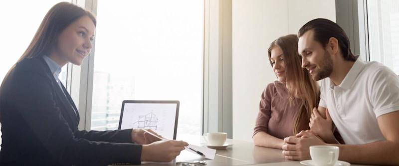 Female realtor meeting with young couple in real estate agency office.