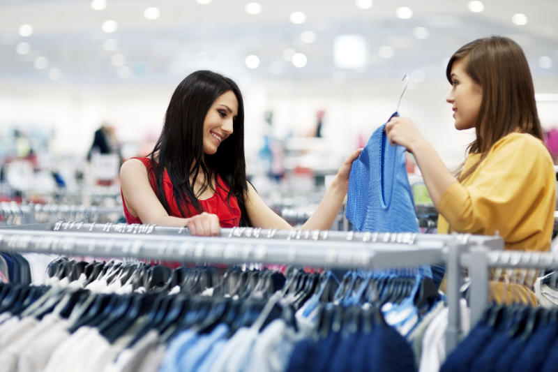 Two shoppers picking out shirts.