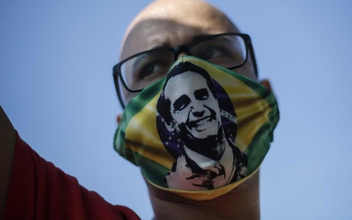 A supporter of Jair Bolsonaro wears a face mask with the president's image - Getty Images