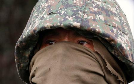 A masked member of Philippine Marines is pictured as his team advance their positions in Marawi City in southern Philippines May 28, 2017. REUTERS/Erik De Castro
