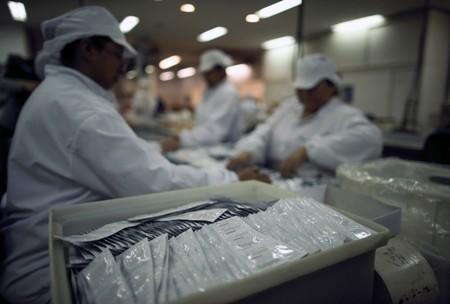 Condoms are seen as employees work in a factory in Buenos Aires