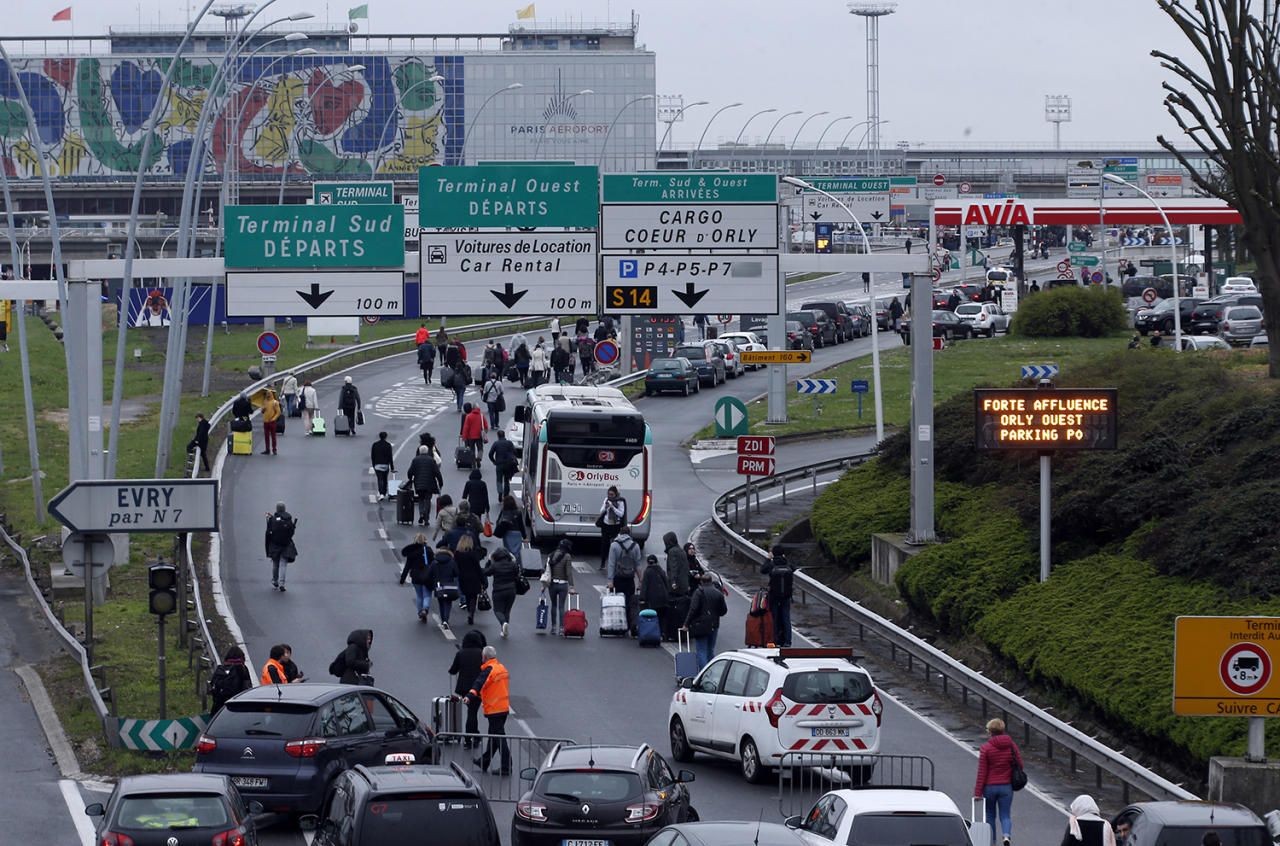 <p>Travellers walk on the highway to the Orly airport, south of Paris, Saturday, March, 18, 2017. A man was shot to death Saturday after trying to seize the weapon of a soldier guarding Paris' Orly Airport, prompting a partial evacuation of the terminal, police said. (AP Photo/Thibault Camus) </p>