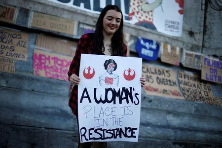 FILE PHOTO: A woman holds a banner during a gathering to mark International Women's Day in downtown Lisbon, Portugal March 8, 2017. REUTERS/Rafael Marchante/File Photo
