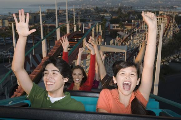 People on a roller coaster with their hands up, smiling