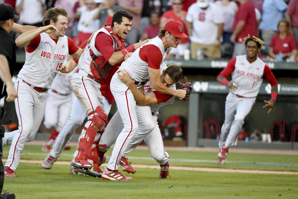 North Carolina State players, left to right, Dalton Feeney (19), Luca Tresh (24), Evan Justice (34) and Austin Murr (12) celebrate after beating Arkansas 3-2 to advance to the College World Series during an NCAA college baseball super regional game Sunday, June 13, 2021, in Fayetteville, Ark. (AP Photo/Michael Woods)