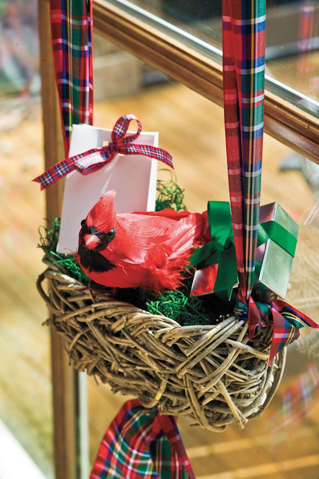 <p>When hosting a holiday party, let your festive decorations double as fun goodie bags. Arrange them in your home's main entry and exit so that upon their arrival, guests are greeted with merry goodies. Pictured above, the holiday hostess displays faux cardinal ornaments on top of a rustic holiday basket of treats. The baskets will then be given as parting gifts to departing guests. You can customize your own goodie bags with containers and treats that compliment your holiday décor. Try metallic boxes filled with chocolate truffles to match elegant decor, or cellophane bags with colorful candies for a children's Christmas party.</p>