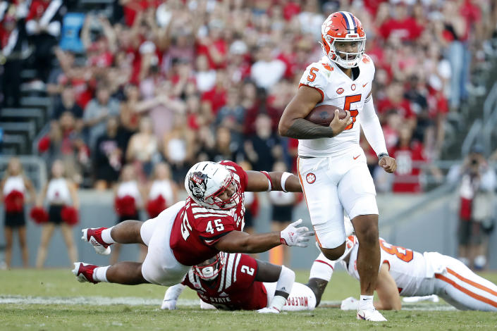Clemson's D.J. Uiagalelei (5) runs away from North Carolina State's Davin Vann (45) during the second half of an NCAA college football game in Raleigh, N.C., Saturday, Sept. 25, 2021. (AP Photo/Karl B DeBlaker)