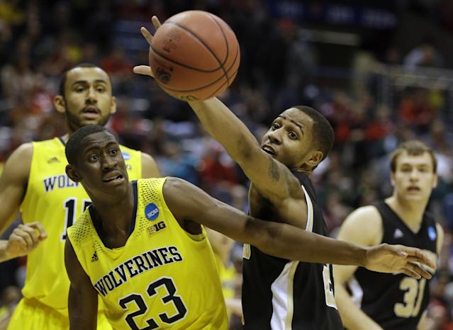 Michigan guard Caris LeVert (23) and Wofford guard Jaylen Allen battle for a rebound during the first half of a second round NCAA college basketball tournament game Thursday, March 20, 2014, in Milwaukee. (AP Photo/Jeffrey Phelps)
