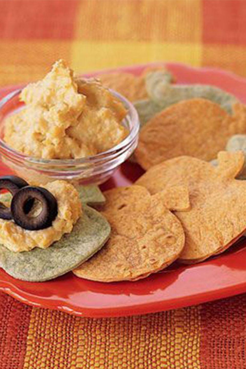 """<p>Pumpkin-shaped chips + hummus = a healthy and hearty snack for your Halloween party. </p><p><a href=""""https://www.womansday.com/food-recipes/food-drinks/recipes/a37174/pumpkin-tortilla-chips-recipe-ghk1005/"""" rel=""""nofollow noopener"""" target=""""_blank"""" data-ylk=""""slk:Get the &quot;Pumpkin&quot; Tortilla Chips recipe."""" class=""""link rapid-noclick-resp""""><em>Get the """"Pumpkin"""" Tortilla Chips recipe.</em></a></p>"""