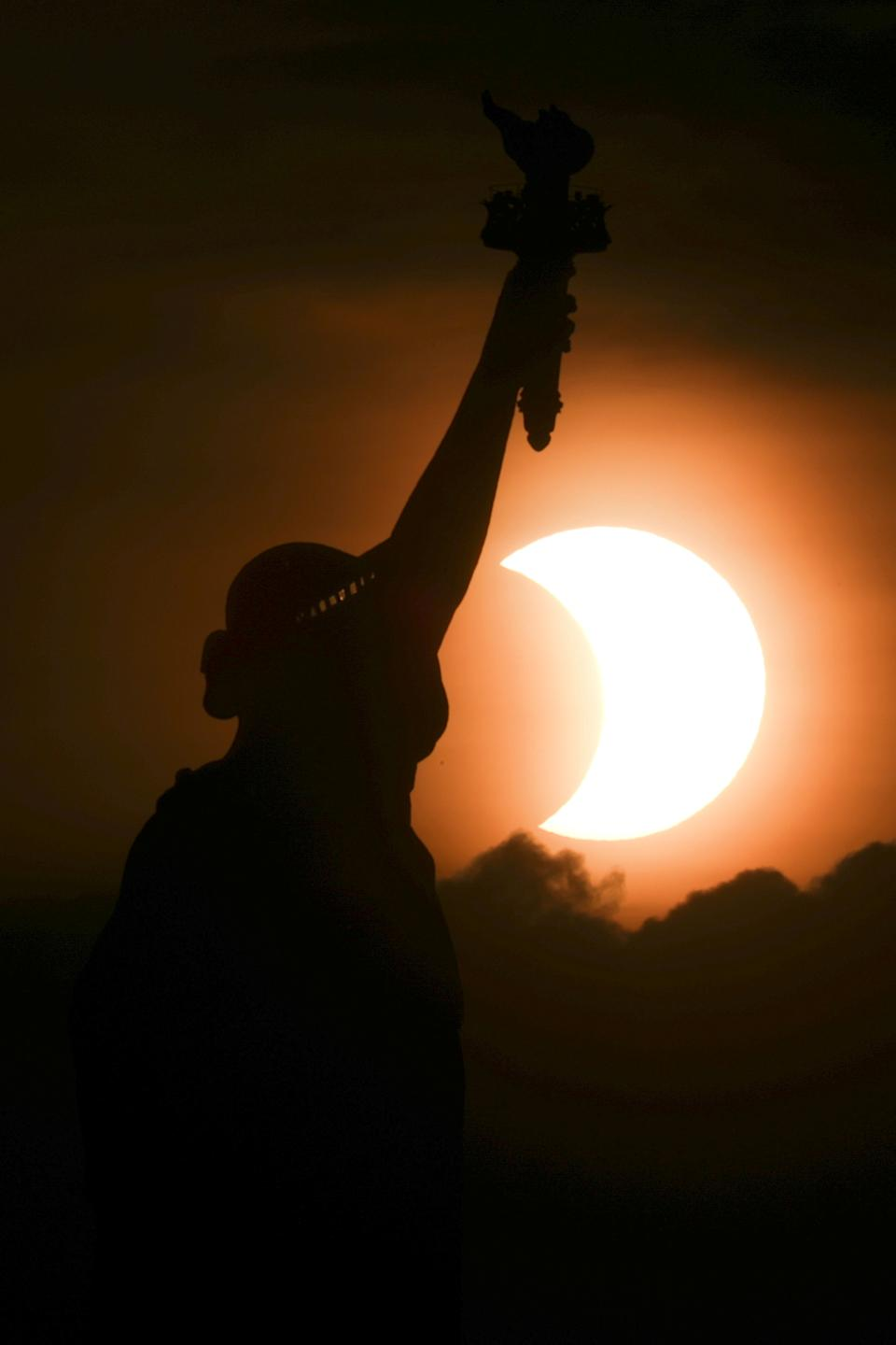 The partially eclipsed sun rises behind the Statue of Liberty in New York City, New York, U.S., early on June 10, 2021. REUTERS/Bjoern Kils/New York Media Boat     TPX IMAGES OF THE DAY