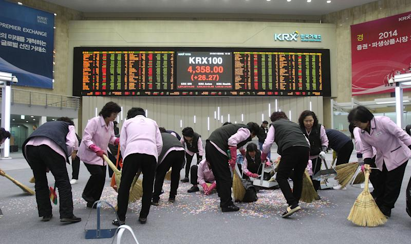 Workers sweep confetti with the brooms after the year's market market closing ceremony near a screen showing the Korea Composite Stock Price Index (KOSPI) at the Korea Exchange in Seoul, South Korea, Monday, Dec. 30, 2013. The Korea Composite Stock Price Index closed the year's last trading at 2,011.34. (AP Photo/Ahn Young-joon)