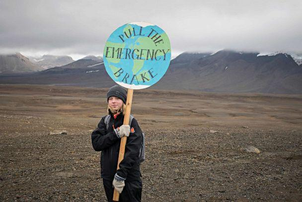 PHOTO: An Icelandic girl poses for a photo with a 'Pull the emergency brake' sign near to where a monument was unveiled at the site of Okjokull, Iceland's first glacier lost to climate change in the west of Iceland on Aug. 18, 2019. (Jeremie Richard/AFP via Getty Images)