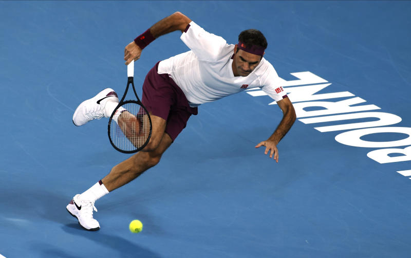 Switzerland's Roger Federer runs to make a backhand return to Hungary's Marton Fucsovics during their fourth round singles match at the Australian Open tennis championship in Melbourne, Australia, Sunday, Jan. 26, 2020.(AP Photo/Andy Wong)