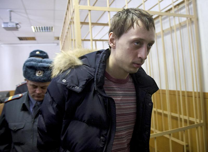 Pavel Dmitrichenko, foreground, is escorted out of a courtroom in Moscow, Russia, on Thursday, March 7, 2013. The star dancer accused of masterminding the attack on the Bolshoi ballet chief acknowledged Thursday that he gave the go-ahead for the attack, but told a Moscow court that he did not order anyone to throw acid on the artistic director's face. The judge, however, refused to release Bolshoi soloist Pavel Dmitrichenko on bail and ordered him held until at least Apr. 18 while the investigation continued. (AP Photo/Ivan Sekretarev)