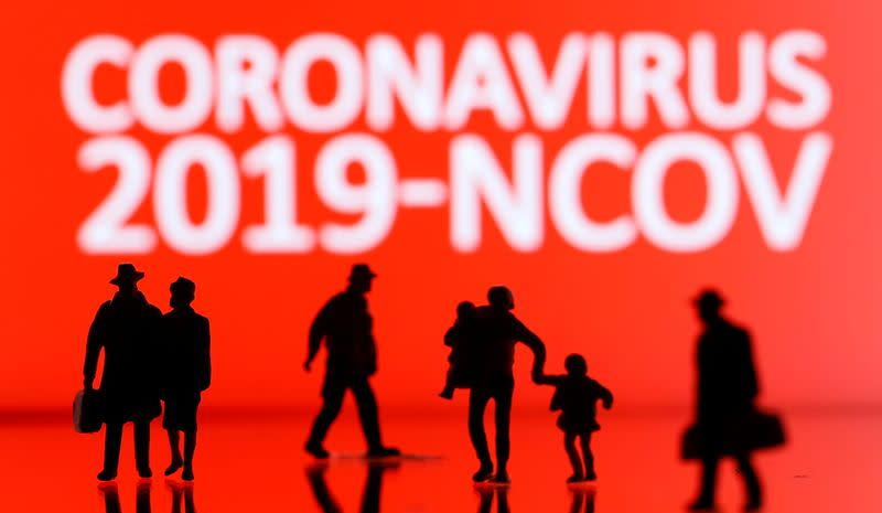 Small toy figures are seen in front of the coronavirus sign