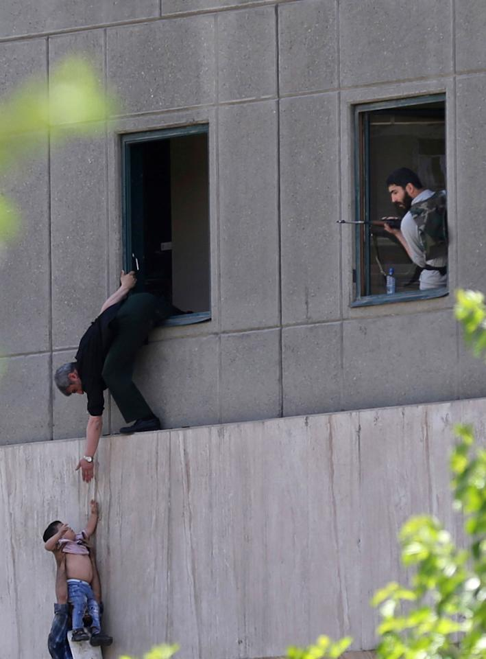 <p>A man hands a child to a security guard from Iran's parliament building after an assault of several attackers, in Tehran, Iran, Wednesday, June 7, 2017. (Photo: Fars News Agency, Omid Vahabzadeh via AP) </p>