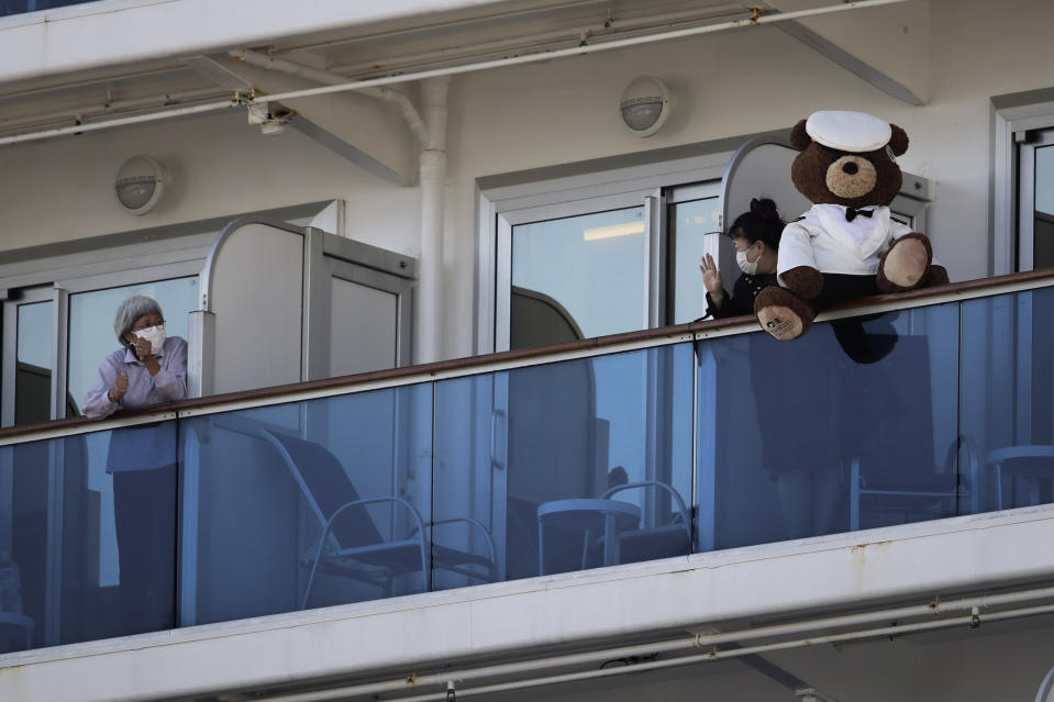 FILE - In this Feb. 11, 2020, file photo, a woman with a teddy bear waves to another passenger quarantined on the Diamond Princess cruise ship in Yokohama, near Tokyo. Life on board the luxury cruise ship, which has dozens of cases of a new virus, can include fear, excitement and soul-crushing boredom, according to interviews by The Associated Press with passengers and a stream of tweets and YouTube videos. (AP Photo/Jae C. Hong, File)
