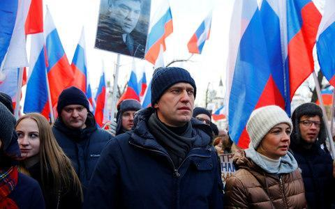 <span>Opposition leader Alexei Navalny, who has been barred from the presidential race, marches in front of Mr Nemtsov's portrait</span> <span>Credit: Sefa Karacan/Anadolu Agency/Getty Images </span>