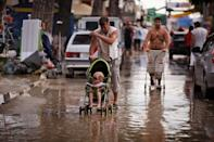 People walk in a muddy street after flooding in the Black Sea resort of Gelendzhik, southern Russia, Saturday, July 7, 2012. Torrential rains dropped nearly a foot of water in the Black Sea region of southern Russia overnight, unleashing intense flooding that killed over a hundred people and forced many to scramble out of their beds for refuge in trees and on roofs, officials said Saturday. (AP Photo/Ignat Kozlov)
