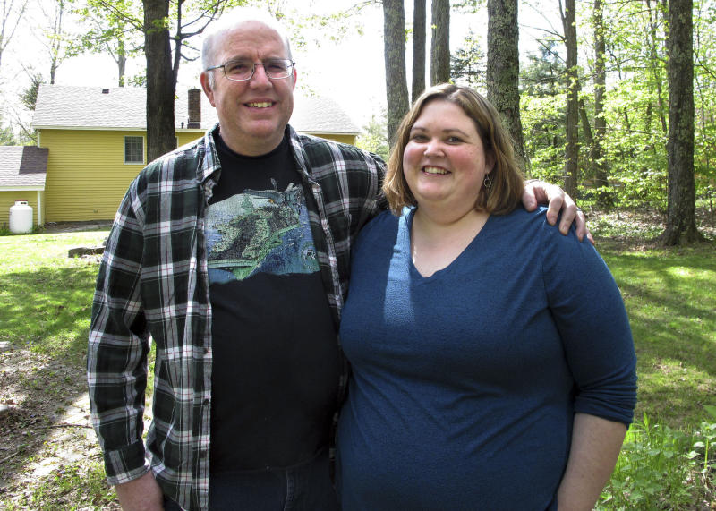 In this May 15, 2019, photo, Jonathan and Beth Dow stand in their backyard in Bennington, Vt. The couple recently moved to Vermont from Colorado through a Vermont program to attract new residents. (AP Photo/Lisa Rathke)