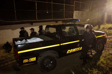 Policemen place the body of a guard killed after a riot by underage inmates in a pickup truck, outside the Correctional Center Stage 2, in San Jose Pinula
