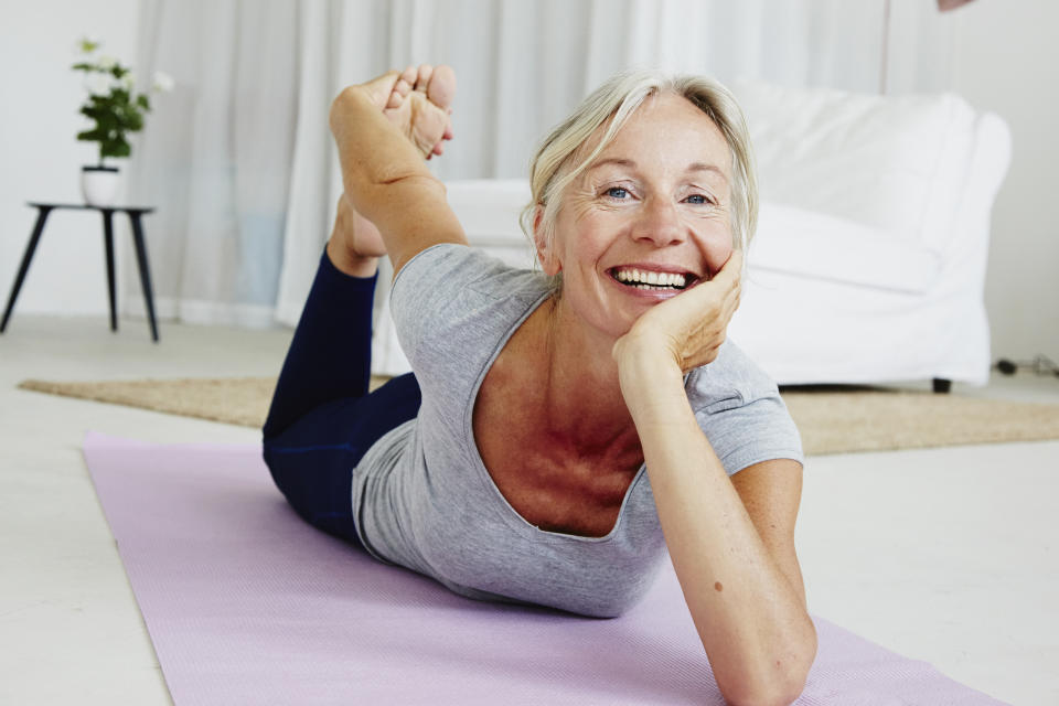 happy senior woman sitting on a yoga mat doing her exercise