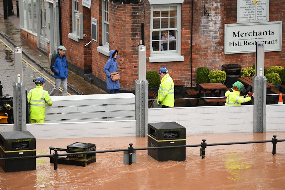 "Environment agency workers put up flood defences in floodwater after the River Severn bursts it's banks in Bewdley, west of Birmingham on February 16, 2020, after Storm Dennis caused flooding across large swathes of Britain. - As Storm Dennis sweeps in, the country is bracing itself for widespread weather disruption for the second weekend in a row. Experts have warned that conditions amount to a ""perfect storm"", with hundreds of homes at risk of flooding. (Photo by Oli SCARFF / AFP) (Photo by OLI SCARFF/AFP via Getty Images)"