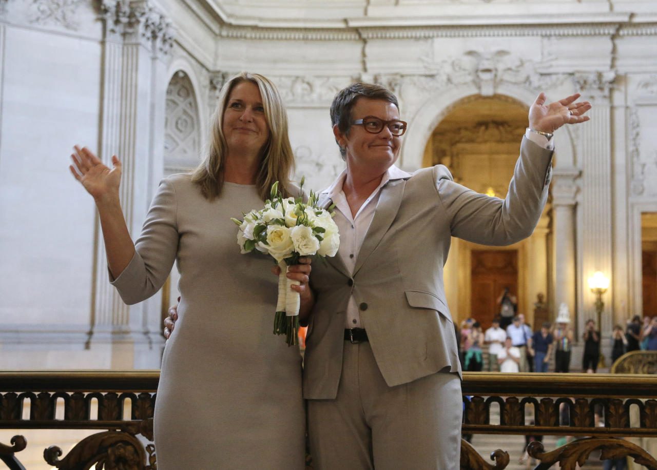 Sandy Stier, left, and Kris Perry wave at supporters after they were wed by California Attorney General Kamala Harris at City Hall in San Francisco, Friday, June 28, 2013. Stier and Perry, the lead plaintiffs in the U.S. Supreme Court case that overturned California's same-sex marriage ban, tied the knot about an hour after a federal appeals court freed same-sex couples to obtain marriage licenses for the first time in 4 1/2 years. (AP Photo/Marcio Jose Sanchez)