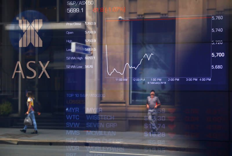 Pedestrians are reflected in a window in front of a board displaying stock prices at the Australian Securities Exchange in Sydney