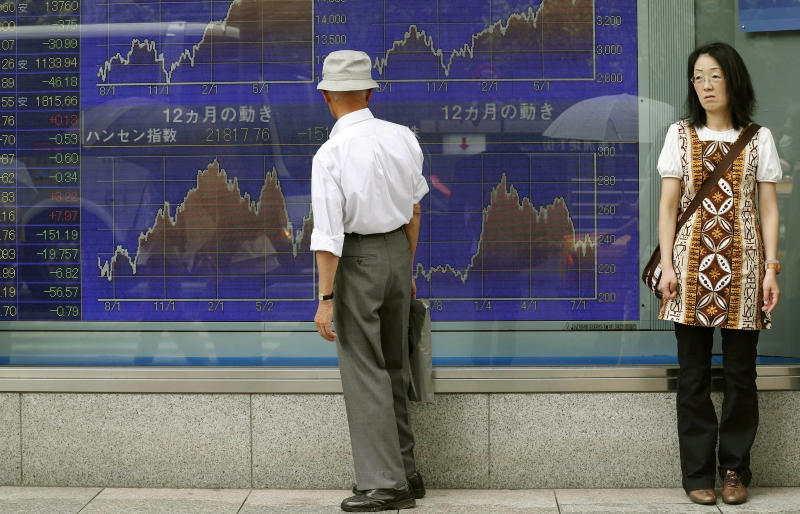 A man looks at an electronic stock board of a securities firm in Tokyo, Monday, July 29, 2013. Asian stock markets fell Monday as traders await a packed schedule of data releases this week in the U.S. and a key meeting of the Federal Reserve. Japan's benchmark Nikkei 225 dropped 2.5 percent to 13,766.09 as the yen continued to reverse from its recent fall. (AP Photo/Koji Sasahara)