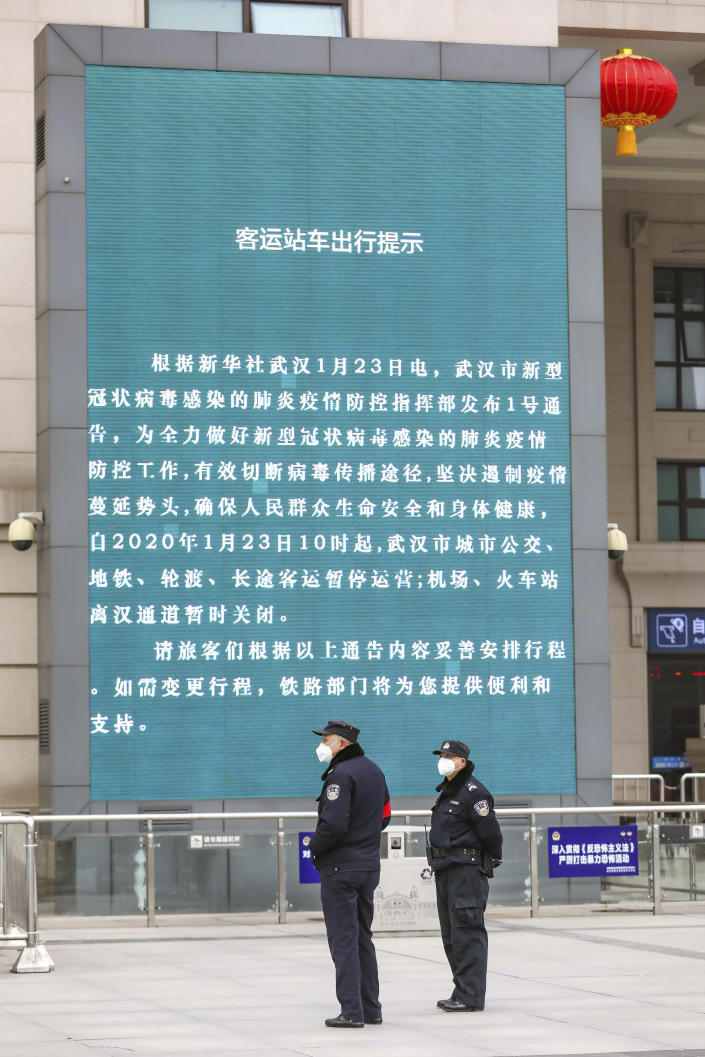 Police stand near a billboard announcing the closure Hankou Railway Station in Wuhan in central China's Hubei Province, Thursday, Jan. 23, 2020. China closed off a city of more than 11 million people Thursday in an unprecedented effort to try to contain a deadly new viral illness that has sickened hundreds and spread to other cities and countries amid the Lunar New Year travel rush. (Chinatopix via AP)