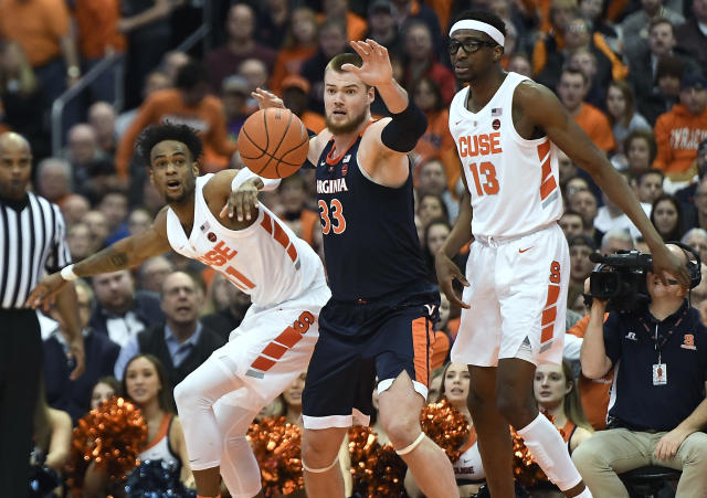 Syracuse forward Oshae Brissett, left, and center Paschal Chukwu, right, watch the ball with Virginia center Jack Salt (33) during the second half of an NCAA college basketball game in Syracuse, N.Y., Monday, March 4, 2019. (AP Photo/Adrian Kraus)
