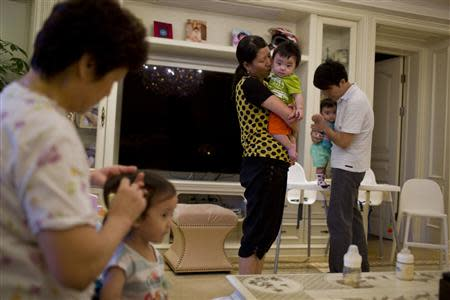 A nanny holds a child of Tony Jiang (back R) at his house in Shanghai September 16, 2013. REUTERS/Aly Song