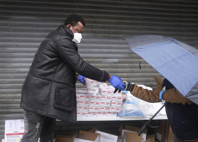 Alex Poam, left, sells gloves to a customer on a street corner in Manhattan, New York, Sunday, April 26, 2020. Poam is studying to be a computer and network technician; after taking online classes most mornings he sells PPE to pedestrians to support himself. (AP Photo/Seth Wenig)