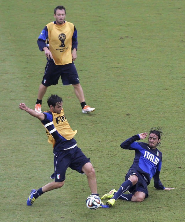 Italy's Marco Parolo, left, is tackled by his teammate midfielder Alberto Aquilani, right, as Italy forward Antonio Cassano looks them during a training session the day before their group D World Cup soccer match, at the Arena das Dunas in Natal, Brazil, Monday, June 23, 2014. (AP Photo/Antonio Clanni)