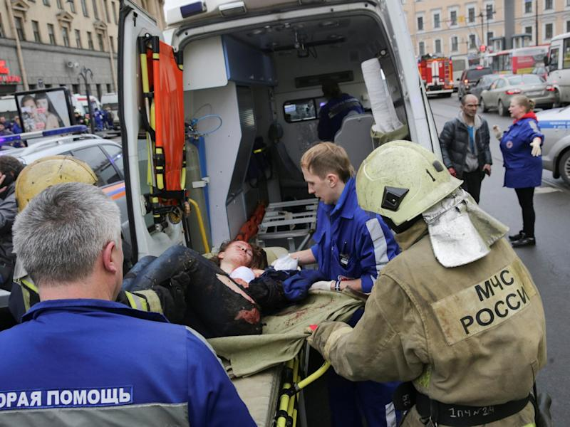 An injured person is helped by emergency services outside Sennaya Ploshchad metro station, following explosions in two train carriages at metro stations in St. Petersburg: Reuters
