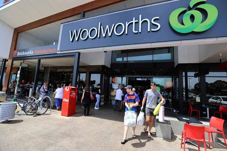 People with bags walking out of a Woolworths store. Source: Getty Images