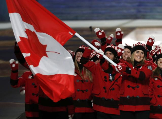 Canada's flag-bearer Hayley Wickenheiser leads her country's contingent during the athletes' parade at the opening ceremony of the 2014 Sochi Winter Olympics, February 7, 2014. REUTERS/Phil Noble (RUSSIA - Tags: OLYMPICS SPORT)