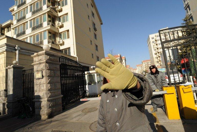 A security guard stops photos being taken outside the compound where Liu Xiaobo and his wife live, on December 28, 2010
