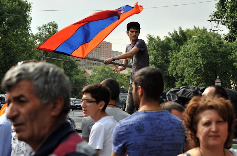 A demonstrator waves an Armenian flag as others block a street during a protest against an increase of electricity prices in Yerevan on June 26, 2015 (AFP Photo/Karen Minasyan)