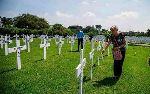 Family members pay their respects to the 915 Dutch soldiers killed in the battle of the Java Sea at the Dutch war cemetery Ereveld in Surabay - Credit: AFP