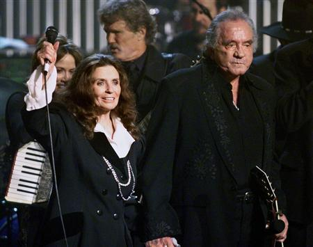 Country music singer-songwriter Johnny Cash and his wife June Carter Cash wave to fans at the end of a tribute in his honor in New York in this file photo taken April 6, 1999. REUTERS/Jeff Christensen/Files