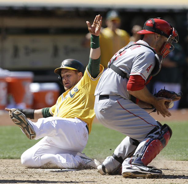Oakland Athletics' Stephen Vogt, left, slides to score past Los Angeles Angels catcher Chris Iannetta in the sixth inning of a baseball game, Sunday, July 28, 2013, in Oakland, Calif. Vogt scored on double by Eric Sogard. (AP Photo/Ben Margot)