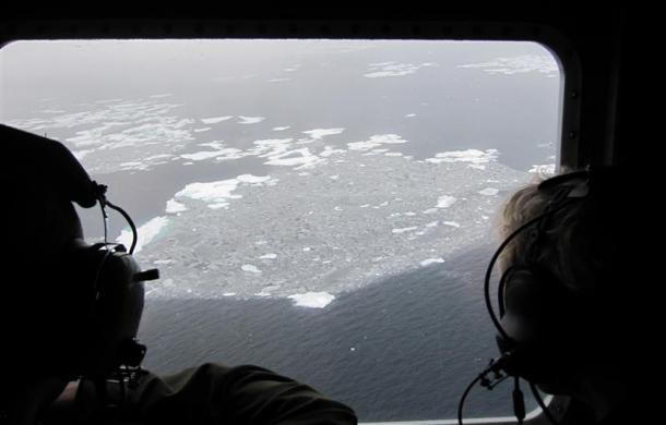 U.S. Coast Guard flight loadmaster Kevin Fox (L) and University of Alaska Fairbanks scientist Rick Steiner survey ice conditions in the Beaufort Sea, about 200 miles from shore, from the window of a Coast Guard C130 September 30, 2009.