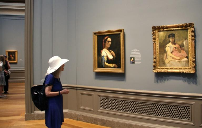 """A woman looks at Jean-Baptiste-Camille Corot's """"Italian Woman (Woman with the Yellow Sleeve)"""" (c. 1870), left, and """" Woman with a Pink Shawl"""" (c. 1865–1870) at the National Gallery of Art in Washington"""