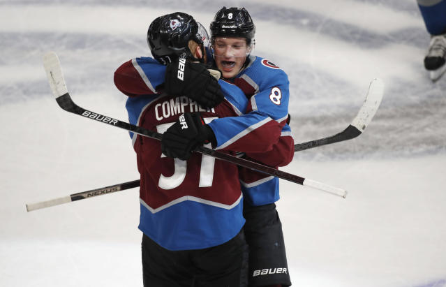 Colorado Avalanche defenseman Cale Makar, back, hugs left wing J.T. Compher, who scored in overtime of the team's NHL hockey game against the New York Rangers on Wednesday, March 11, 2020, in Denver. Colorado won 3-2. (AP Photo/David Zalubowski)