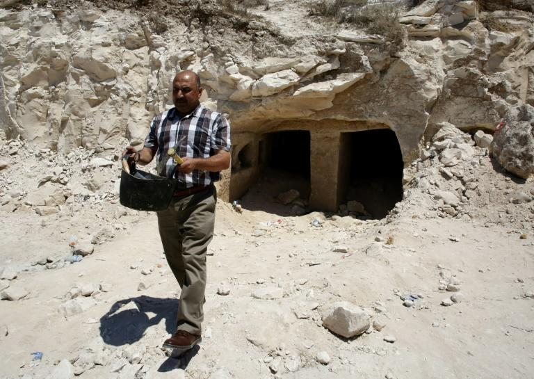 Taleb Jubran, director of the department of tourism and antiquities in Hebron, works at a newly discovered Roman-era burial site in the West Bank on August 16, 2018